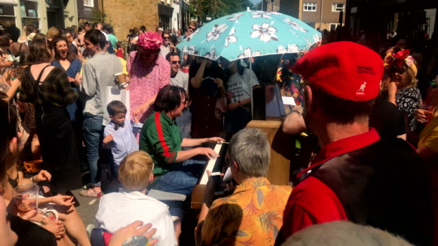 a man plays a piano on the street during a royal wedding street party to celebrate the marriage of prince harry and meghan markle at the wilton way... - street party stock videos and b-roll footage