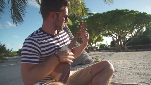 a man plays a ukulele guitar in the tropical islands in french polynesia. - french overseas territory stock videos & royalty-free footage