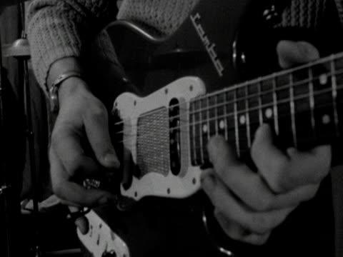 A man plays an electric guitar