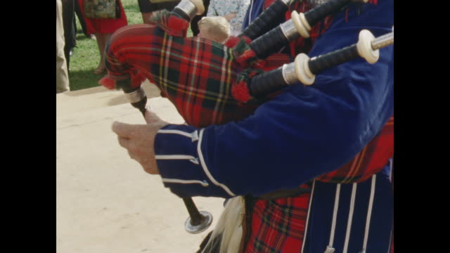 man plays bagpipes as young man performs a highland dance on stage in front of the festival crowd. - bagpipes stock videos & royalty-free footage