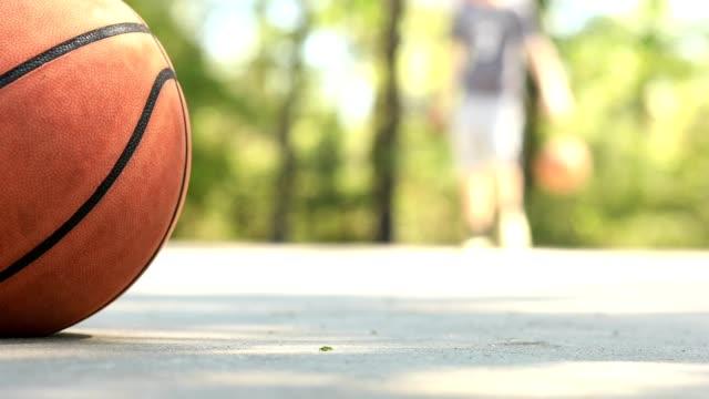 vidéos et rushes de l'homme joue au basket sur le terrain de parc extérieur en été, au printemps. - streetball
