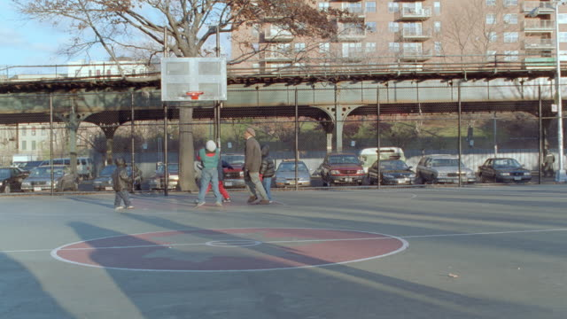 a man plays basketball with several boys at a bronx playground. - basketball ball stock videos & royalty-free footage