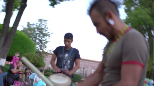 Man plays congas in drumming band in park