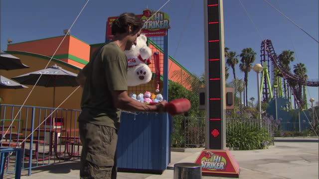 man plays hi-striker midway game test of strength at knott's berry farm theme park, reverse angle - zoom to score - hammer stock videos and b-roll footage