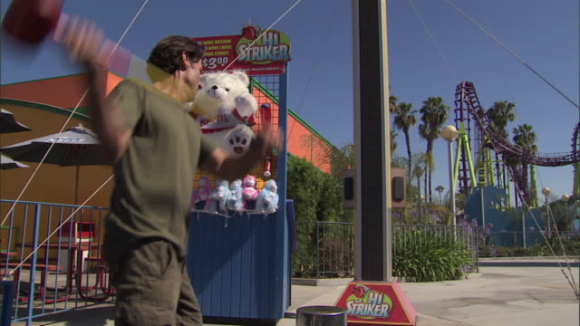 Man plays Hi-Striker midway game test of strength at Knott's Berry Farm theme park, reverse angle - zoom to score