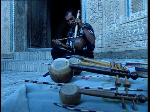 man plays string instrument outside mosque as tourists pass uzbekistan - string instrument stock videos and b-roll footage