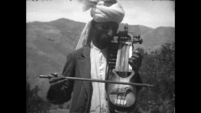 man plays string instrument with bow from the home movies of rww turner - string instrument stock videos and b-roll footage
