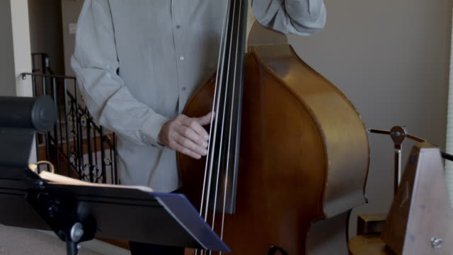 a man plays the bass as he reads music placed on a stand. - music stand stock videos & royalty-free footage