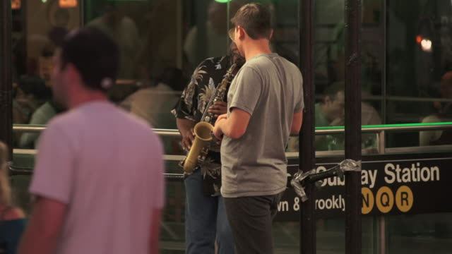 A man plays the sax in front of a subway in Time Square.  People walk by.