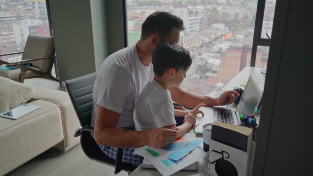 man plays with his son while teleworking - colombian ethnicity stock videos & royalty-free footage