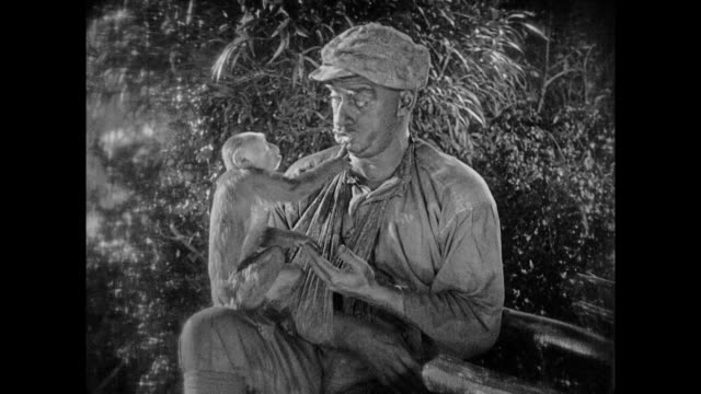 1925 man plays with monkey while talking to man next to hammock - 1925 stock videos & royalty-free footage