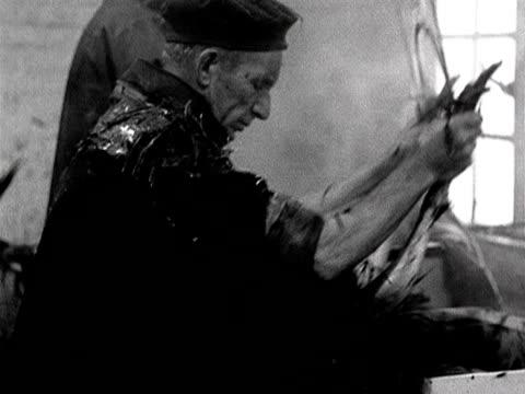 man plucks a turkey using a spinning machine at a turkey farm in wales. 1954. - wirbeltier stock-videos und b-roll-filmmaterial