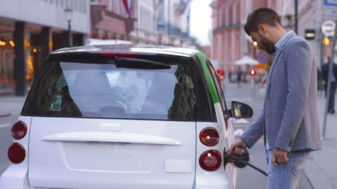 vídeos y material grabado en eventos de stock de slo mo man plugging car at ev station in city - coche híbrido