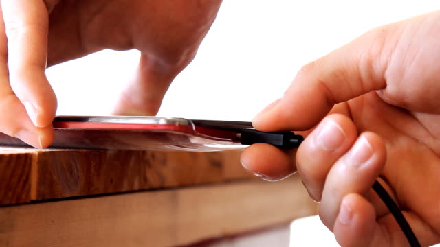 man plugging charging cable into mobile phone on white background - caricare attività video stock e b–roll