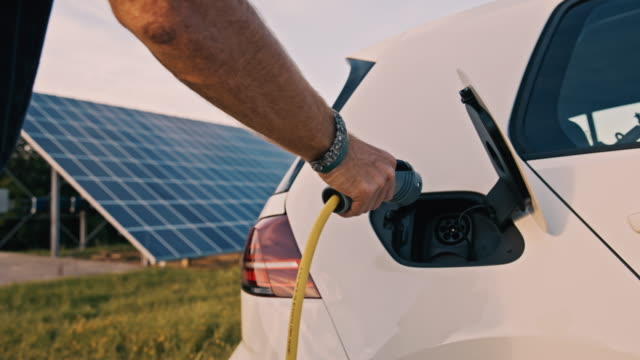 slo mo man plugging his car for charging it from solar energy - renewable energy stock videos & royalty-free footage
