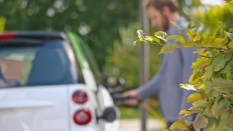 vídeos y material grabado en eventos de stock de ds man plugging in an electric car at home - cargar
