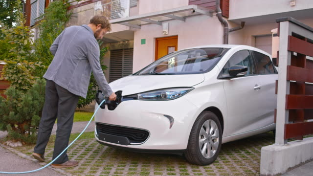 vídeos y material grabado en eventos de stock de ds man plugging in electric car at home - cargar