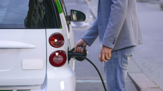 Man plugging in his car at EV station in city