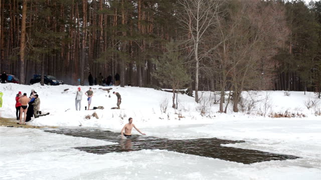 mann stürzt in kaltem wasser während der feier der epiphanie. - gefrorenes wasser stock-videos und b-roll-filmmaterial