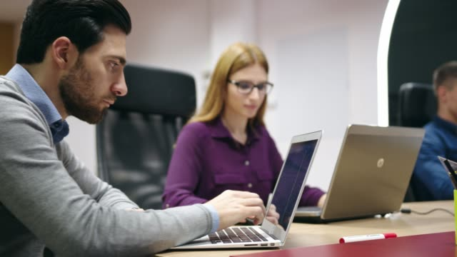 man pointing his finger on laptop screen while working with his colleagues - female with group of males stock videos & royalty-free footage
