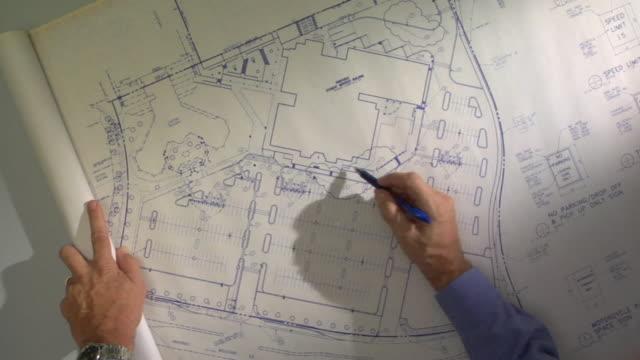POV CU Man pointing to locations on blueprint with pen / Atlanta, Georgia, USA