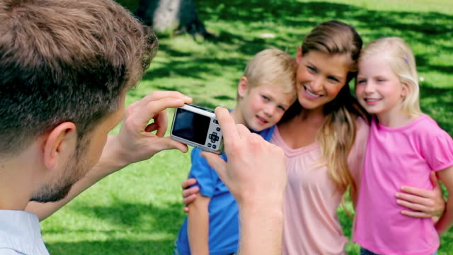 a man takes a photo of his family who are embracing before they turn to the camera and smile - digital camera stock videos and b-roll footage
