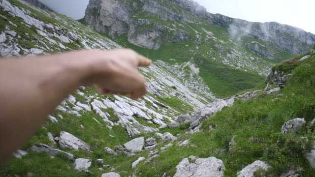A man points at the view in the mountains. - Slow Motion