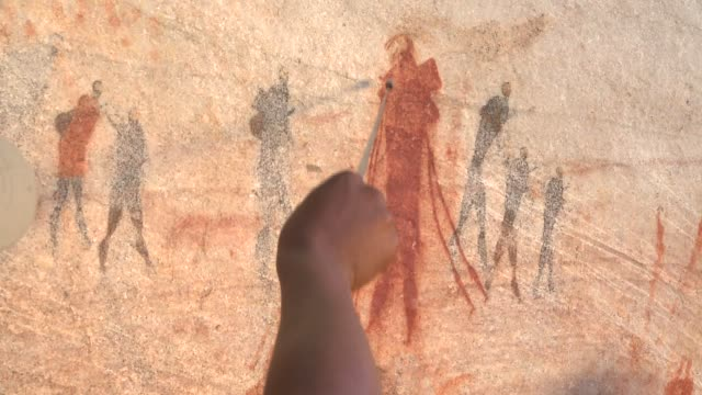 a man points out petroglyphs on a cave wall. available in hd. - cave painting stock videos & royalty-free footage