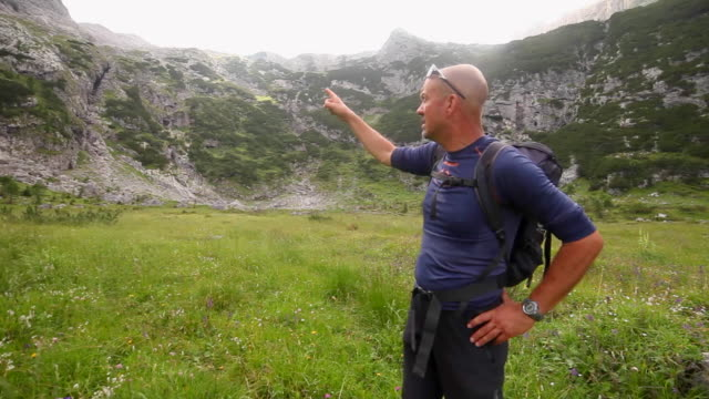 a man points while hiking and backpacking on a trail in the mountains. - completely bald stock videos and b-roll footage