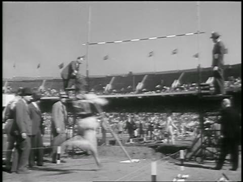 vídeos de stock e filmes b-roll de b/w 1933 rear view man pole vaulting over bar / philadephia / newsreel - 1933