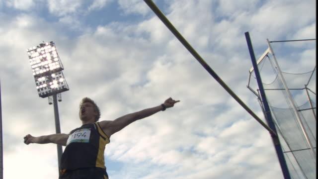 vídeos y material grabado en eventos de stock de la ms man pole vaulting over pole, then cheering / sheffield, england, uk - atlético