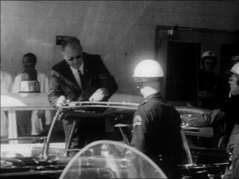 b/w 1963 man policemen examining kennedy's car after assassination / dallas / newsreel - attentat auf john f. kennedy stock-videos und b-roll-filmmaterial