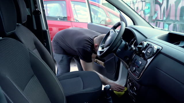 a man polishes a car in a self-service car wash. - lava video stock e b–roll