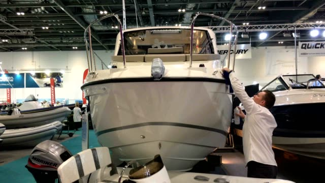 a man polishes the hull of a boat on display at the annual london boat show at excel on january 6 2017 in london england the show runs from the 6th... - london boat show stock videos and b-roll footage