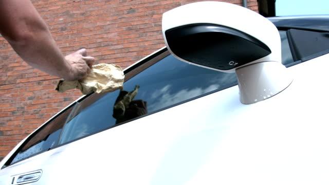 uomo pulizia una finestra auto - avambraccio video stock e b–roll