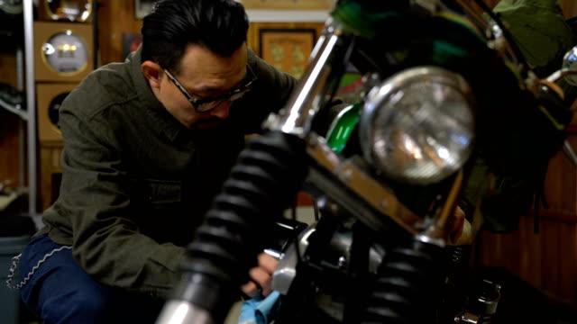 研磨と彼のガレージで彼のカスタム バイクを維持する男 - 機械工点の映像素材/bロール