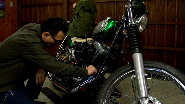 Man polishing and maintaining his custom motorcycle in his garage