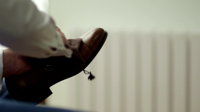 SLO MO CLOSE UP Man polishing brown leather shoe