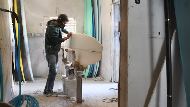 man polishing surfboard at r&d surf workshop in rockledge, fl, u.s. on tuesday, january 19, 2021. - workbench stock videos & royalty-free footage