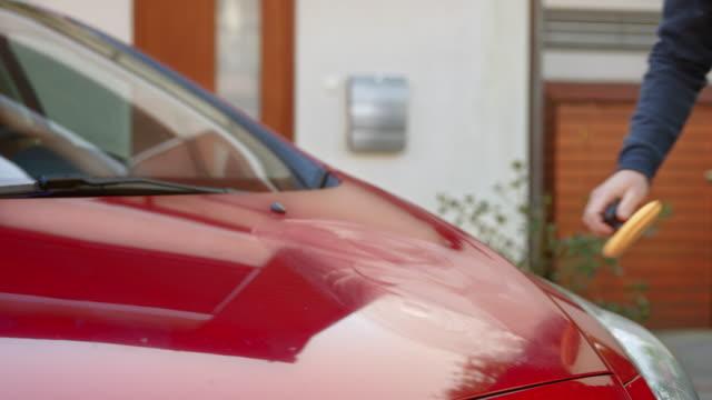 stockvideo's en b-roll-footage met man de motorkap van zijn rode auto polijsten - mouw