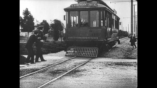 1921 man (buster keaton) poses like a statue to elude the police after he fails to escape from them on a trolley - 1921 stock-videos und b-roll-filmmaterial
