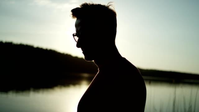 vídeos de stock, filmes e b-roll de homem posando em um cais do lago. pôr do sol - píer