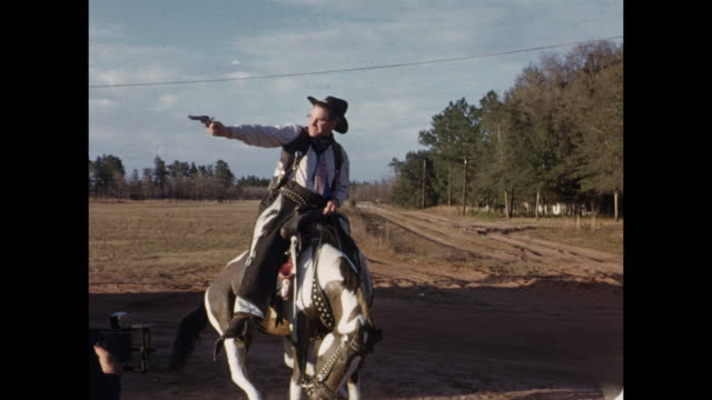 vidéos et rushes de 1954 home movie man posing on bucking bronco statue / united states - homme dans un groupe de femmes