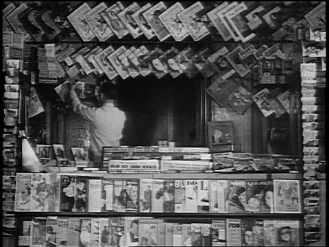 b/w 1935 man posting magazines in newsstand / industrial - zeitschrift stock-videos und b-roll-filmmaterial