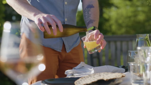 man pouring a beer at a midsummer dinner - solstice stock videos & royalty-free footage