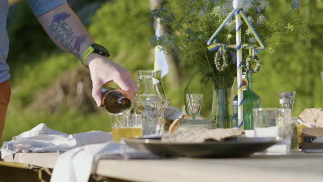 stockvideo's en b-roll-footage met mens die een bier bij een midzomerdiner giet - zomerzonnewende