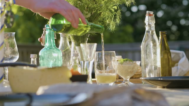 man pouring a beer at a midsummer dinner - swedish culture stock videos & royalty-free footage
