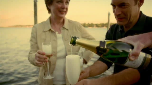 vídeos de stock e filmes b-roll de man pouring champagne into flutes for men and woman on dock / group toasting and sipping champagne - pontão