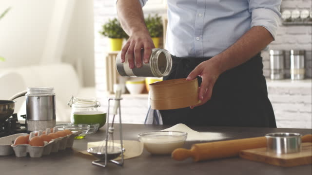 man pouring flour from the jar into flour sifter - kitchen worktop stock videos & royalty-free footage