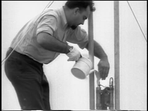 B/W 1933 man pouring fuel into world's first liquidfueled rocket / newsreel